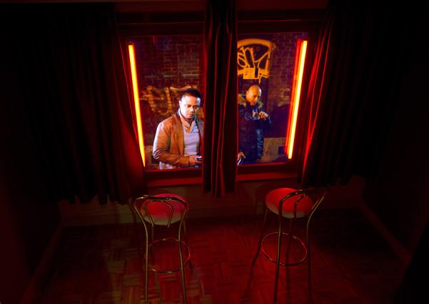 Unos visitantes miran desde fuera un escaparate rojo enel museo de la prostitución delBarrio Rojo de Amsterdam.