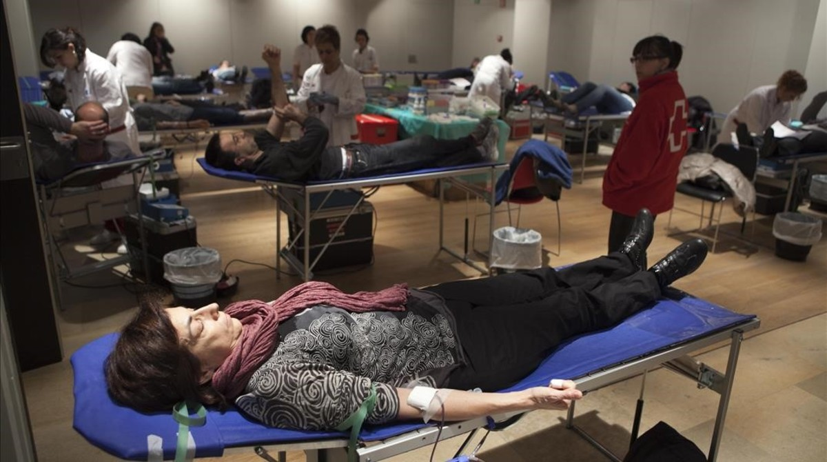 Varios ciudadanos donan sangre en el Palau Robert, en Barcelona.