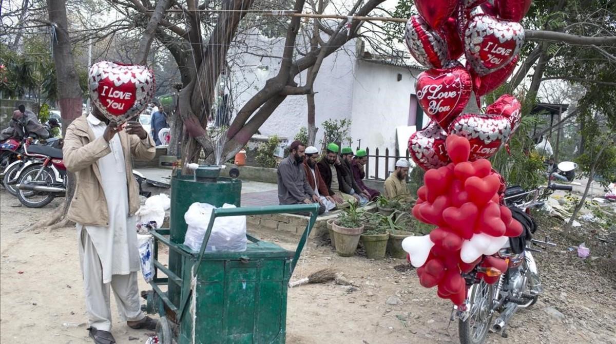 Un vendedor hincha globos de San Valentín al lado de un grupo de personas que rezan, el 14 de febrero del 2017, en Islamabad.