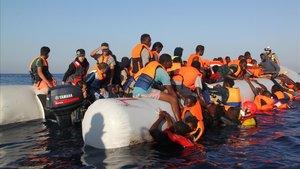 Un socorrista de la oenegé Proactiva Open Arms asiste a varios refugiados durante un rescate.