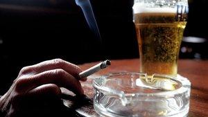 Un usuario fuma un cigarrillo mientras consume un vaso de cerveza en un pub de Belfast,en el norte de Irlanda