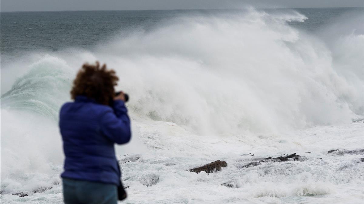 Una mujer fotografía el fuerte oleaje del mar Cantábricoen el pueblo de Rinlo, en Ribadeo (Lugo).