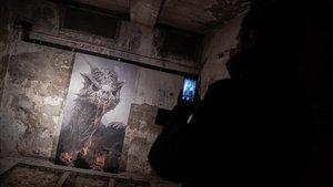 Una mujer fotografia una imagen de la exposición 'Juego de tronos oculto', en Berlín.