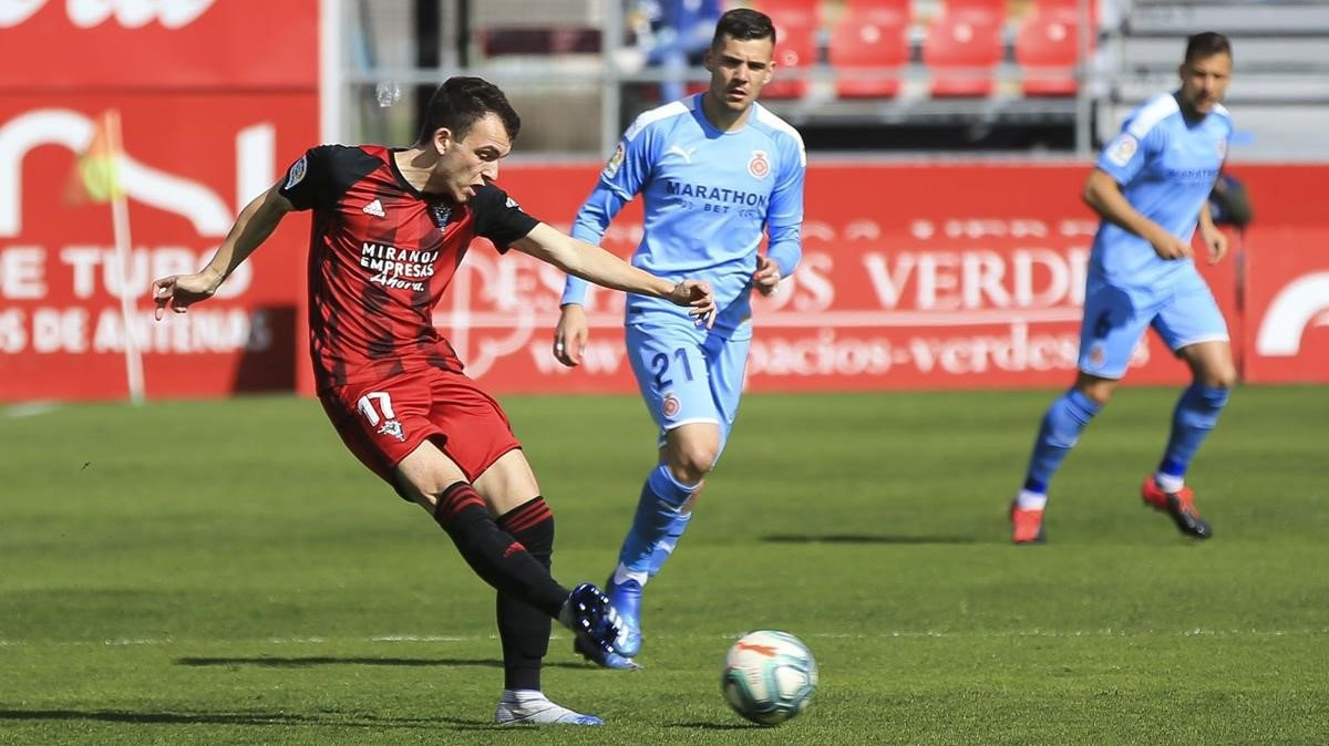 Un jugador del Mirandés enlaza en el centro del campo durante el duelo con el Girona.