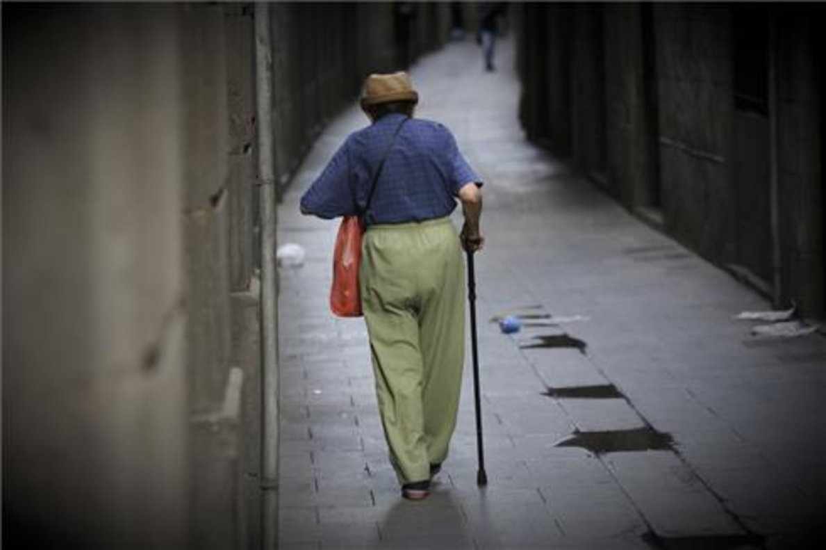 Un anciano camina por las calles de Barcelona.