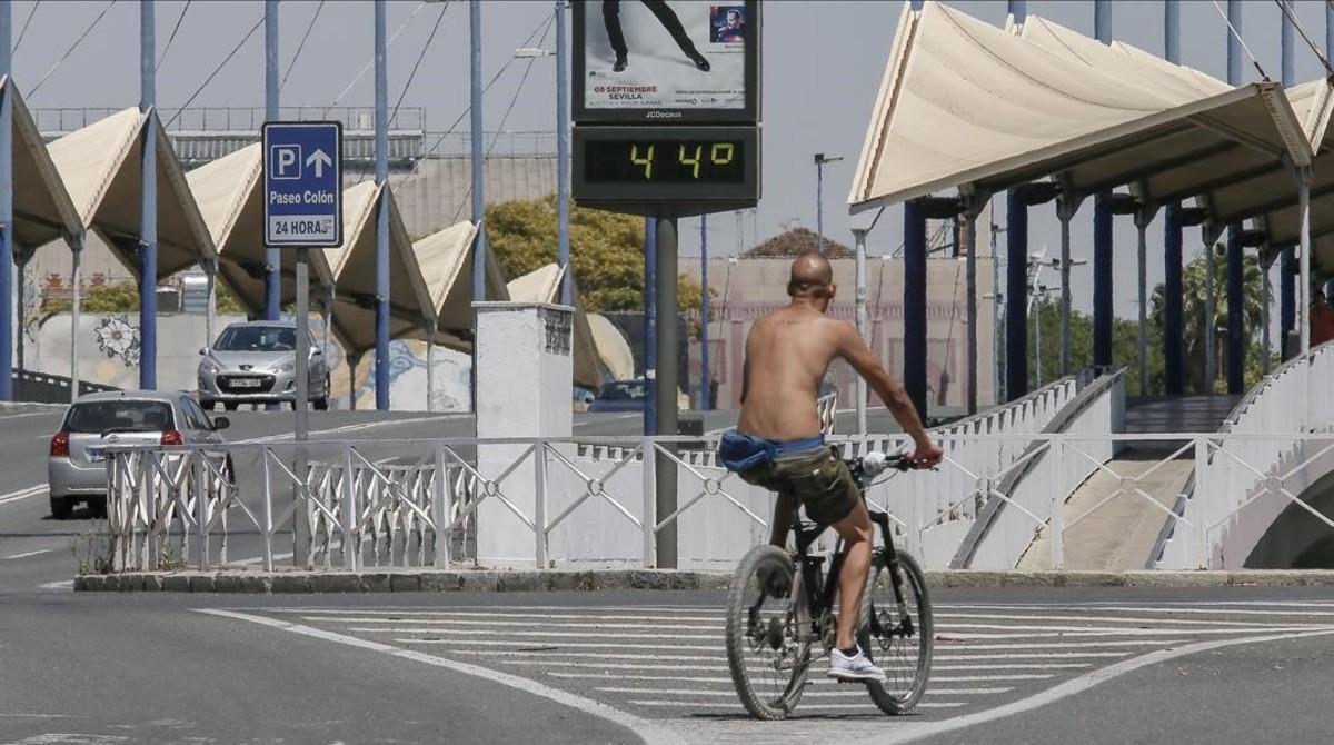 Un ciclista pasa ante un termómetro callejero en Sevillla, el domingo por la tarde. La máxima oficial fue de 39º.