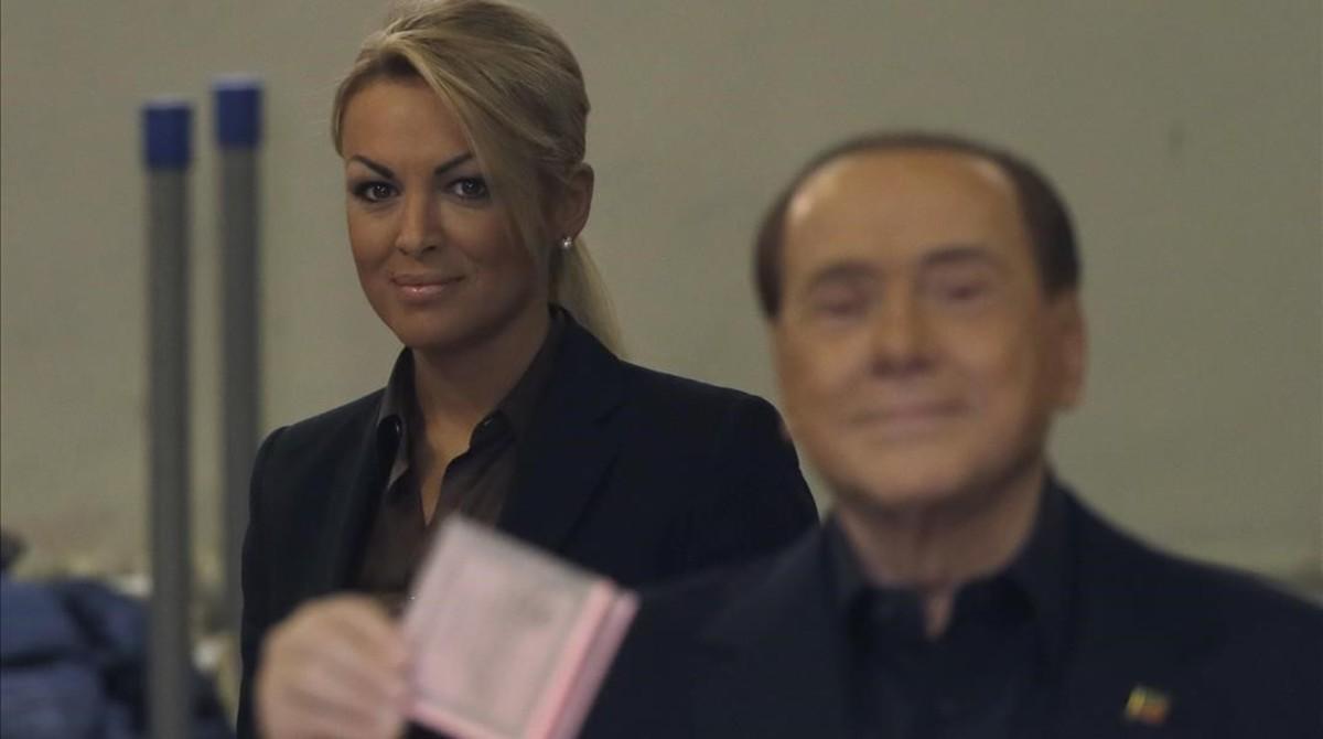 Berlusconi (derecha), flanqueado por su novia actual, Francesca Pascale, en el momento de votar en el referéndum, en Roma, este domingo.