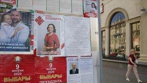 Una mujerpasa junto a unoscarteles electorales de los principales candidatos en Minsk.