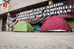 El campamento constituido por tiendas de campaña y sillas de plástico delante de la Oficina de Vivienda.