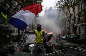 Un chaleco amarillo ondea una bandera francesa entre los destrozos causados durante una protesta en París.