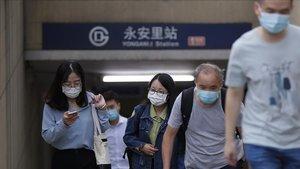 Un grupo de viajeros salen de la boca al metro de una estación de Pekín.