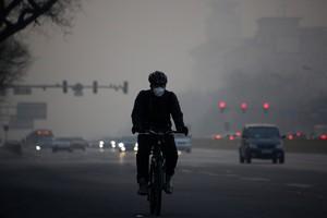 Un ciclista circula por Pekín en un día de alta contaminación.