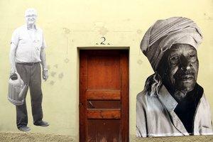 Enuna fachada de Avià, a un lado, un vecino, y en el otro, un hombre de origen africano.
