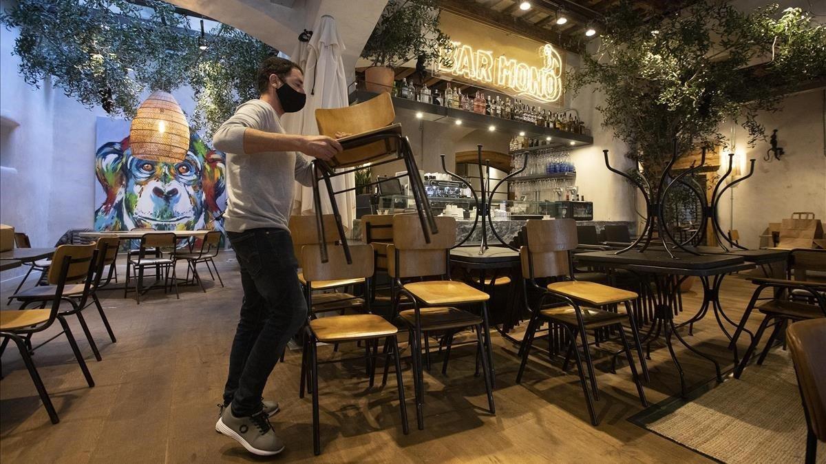 Un hombre coloca sillas en el interior de un bar en el Gòtic de Barcelona, este jueves.