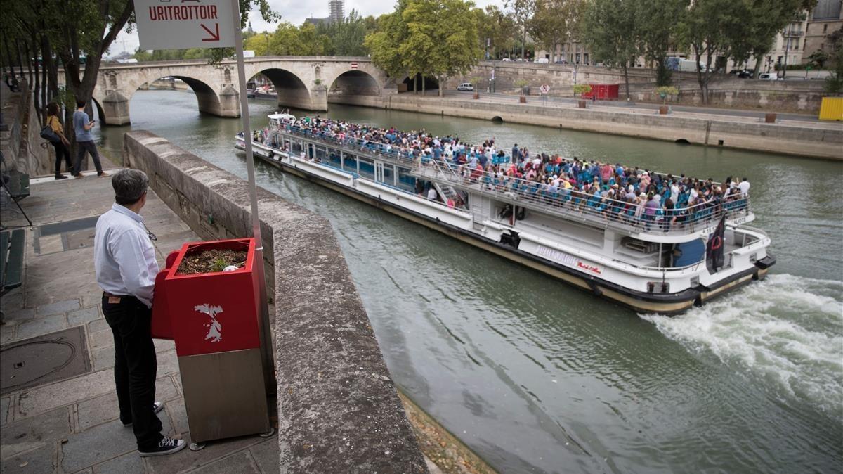Un hombre utiliza un uritrottoir ante el paso de un bateau mouche en el Sena.