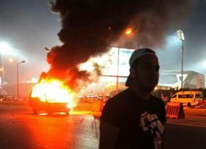 Imágenes de un coche ardiendo este domingo, durante los disturbios en El Cairo.