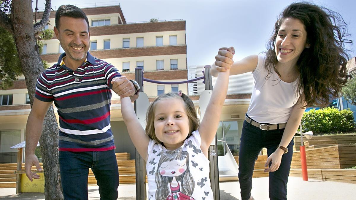 Una familia juega con su hijaafectada por atresia de esófago, este sábado en Barcelona.