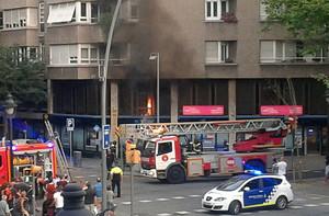 Los bomberos apagan el incendio declarado en la sede de UPDE, en el número 444 de la Gran Via de Barcelona.