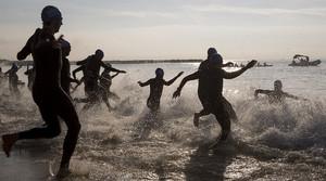 Los participantes en el Triatlón de Barcelona se lanzan al mar, con trajes de neopreno.