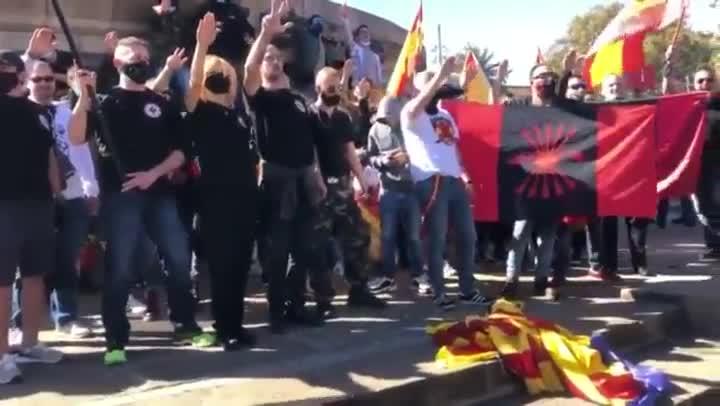 Manifestantes ultras queman una 'estelada' y cantan el 'Cara al sol'.