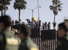 Migrantes en Tijuana, México, miran desde el otro lado del muro durante una visita de la Secretaria de Seguridad, Kirjsten Nielsen.