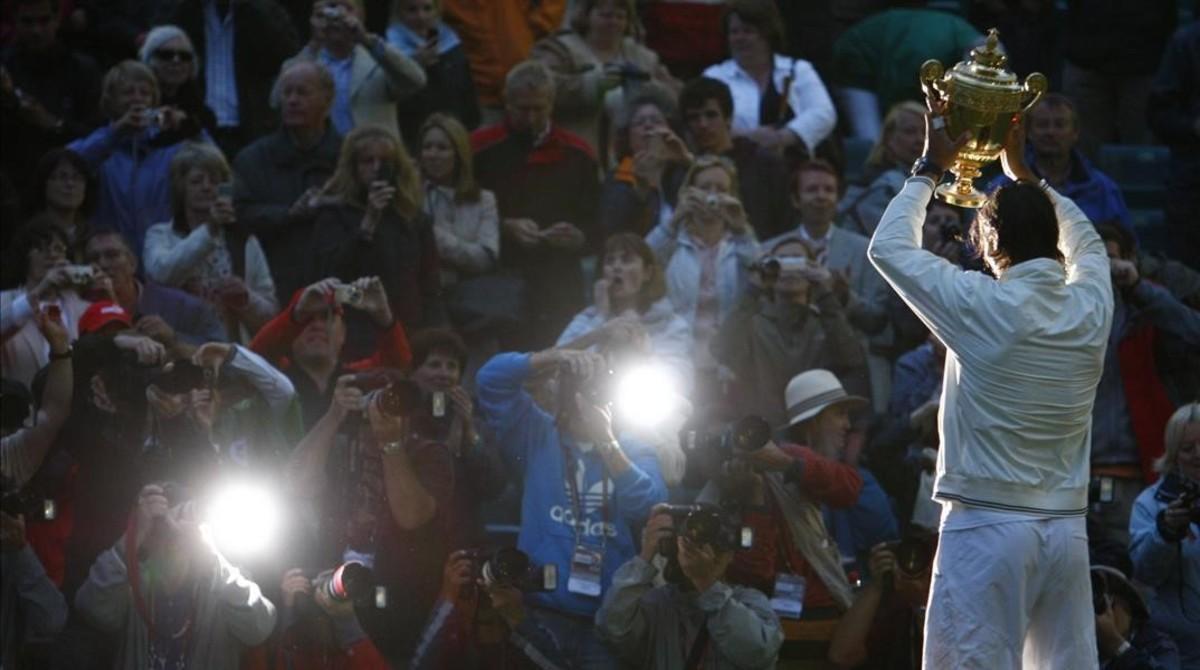 Nadal muestra el trofeo, caída la noche en Wimbledon.
