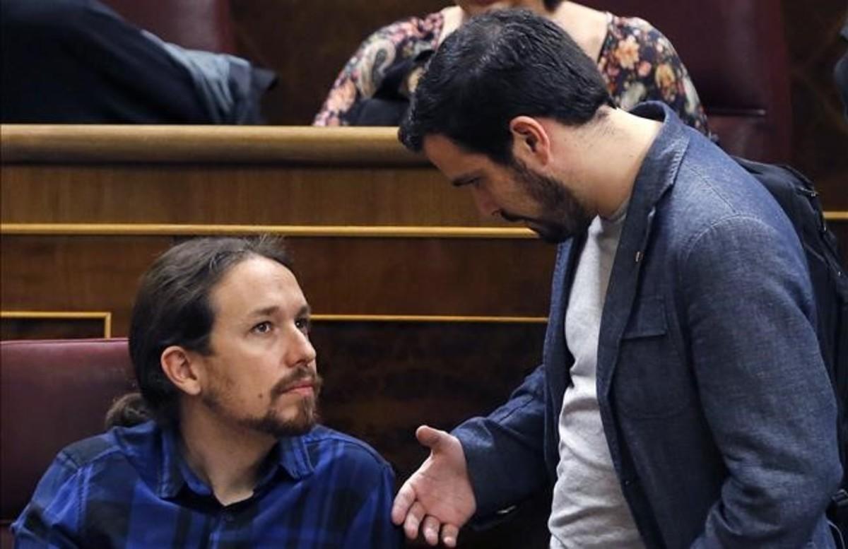 Pablo Iglesias y Alberto Garzón conversan en el hemiciclo del Congreso.