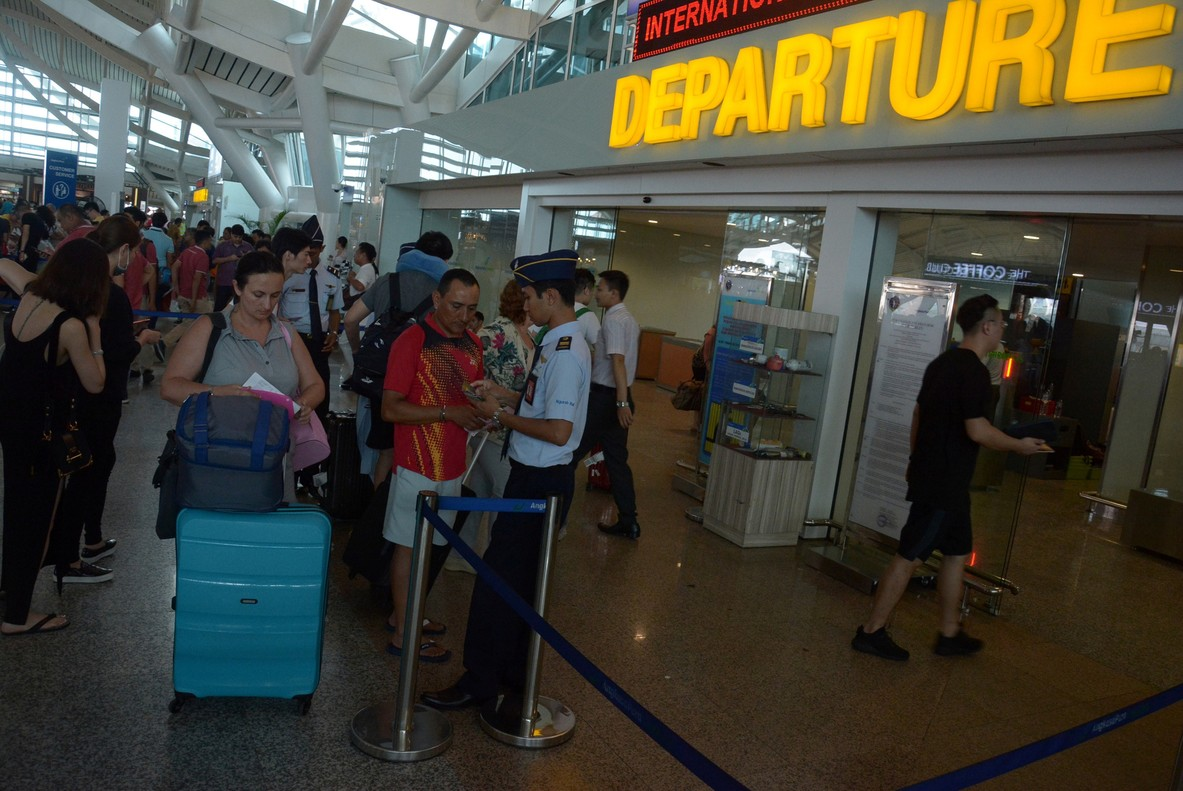 Pasageros haciendo cola en el aeropuerto Ngurah Rai de la isla de Bali, después de que retomara su actividad.