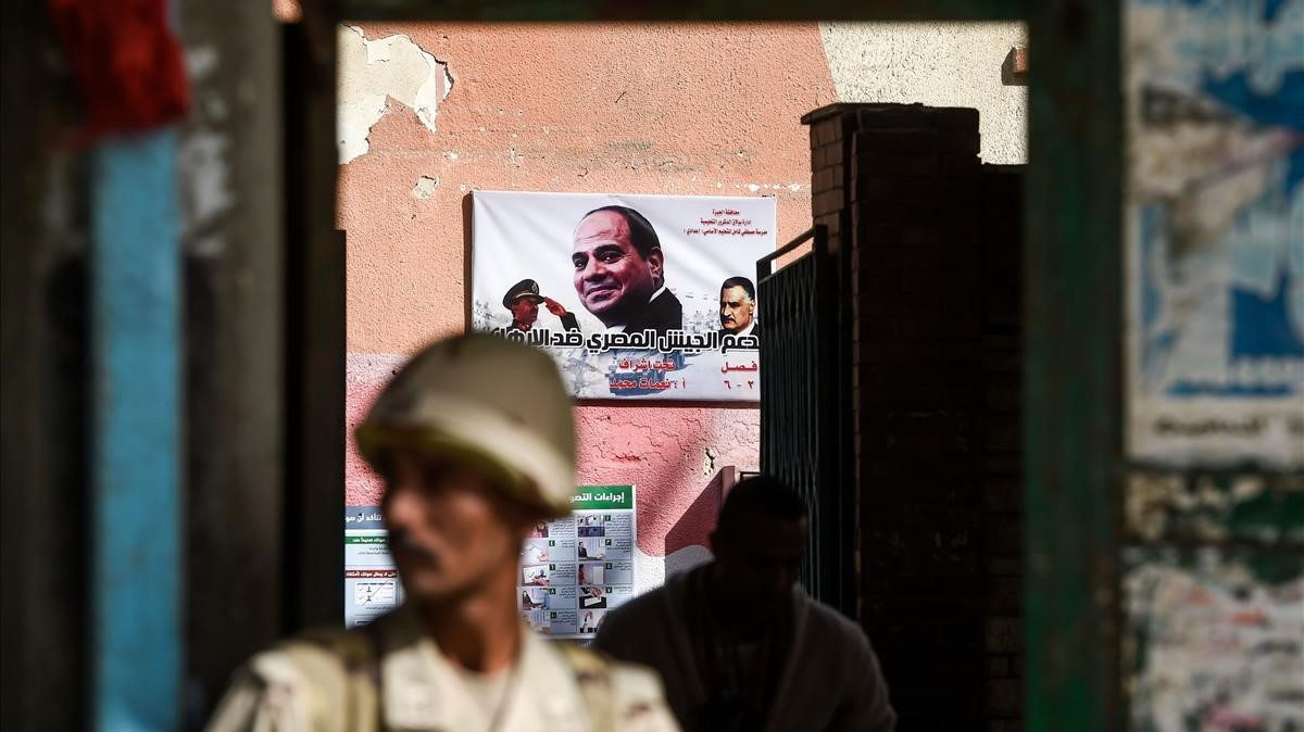 Un soldado custodia un centro de voto con un cartel electoral de Al Sisi.