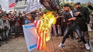 Manifestantes palestinos queman banderas de EEUU e Israel en Gaza.