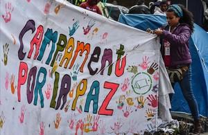 Una joven ayuda a colocar una pancarta a favor del acuerdo de paz en la acampada dela plaza Bolivar, enBogotá.