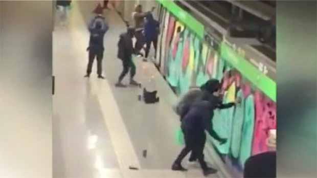 Una vintena de grafiters pinten diversos dels vagons de dos combois de la línia 3 del metro de Barcelona davant la mirada impotent dels guàrdies de seguretat.