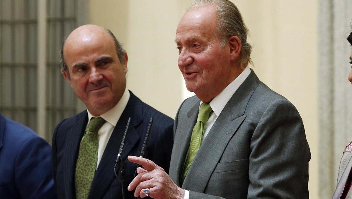 El entonces ministro de Economía, Luis de Guindos, y el rey Juan Carlos, en junio de 2014, en la entrega de un premio.