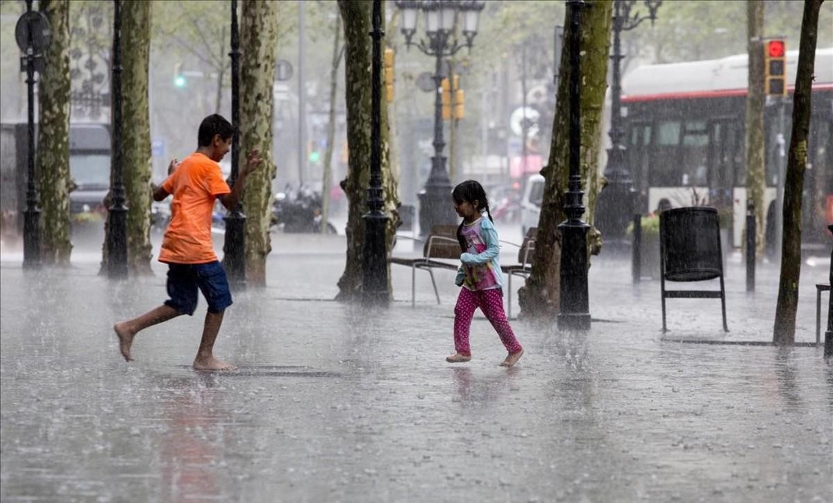 Unos niños juegan bajo la lluvia en el paseo de Gràcia de Barcelona.
