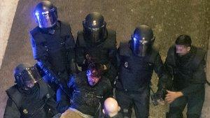 Unos policías detienen a un manifestante durante los altercados producidos en Barcelona, este jueves.