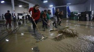 Varias personas intentan limpiar de agua y lodo un local en la localidad cordobesa de Villa del Río.