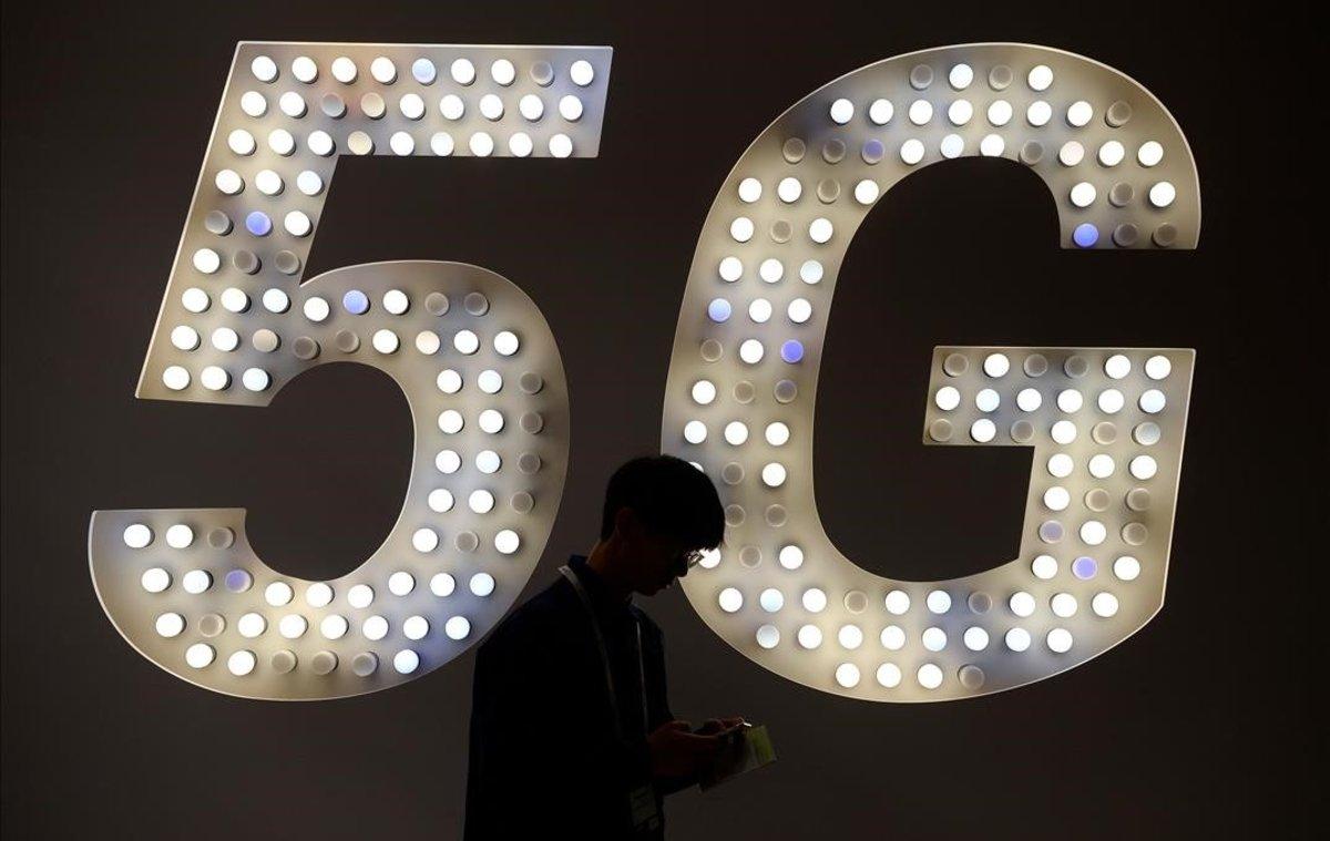 Un visitante usa su teléfono junto a un cartel de 5G en el estand de Intel.