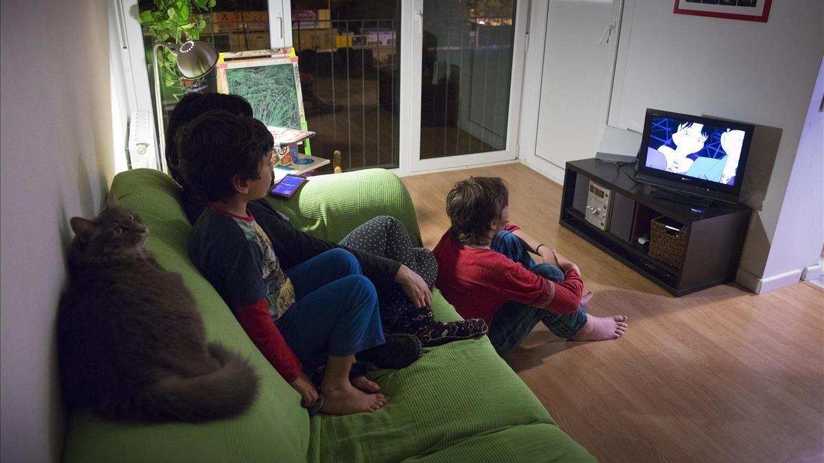 Una familia mira la tele en el salón de su casa.