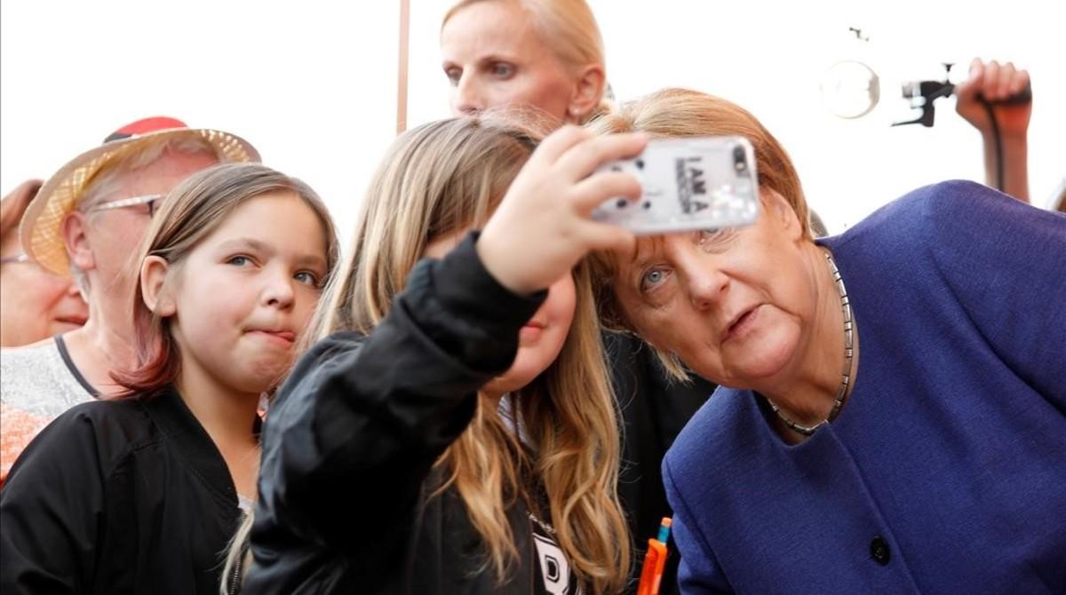 La cancillera alemana, Angela Merkel, se hace un selfi con una seguidora.