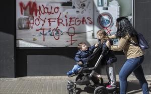 Una joven con sus hijospasa ante una pintada en una calle del barrio de Benimacletque llama al paro de las mujeres.
