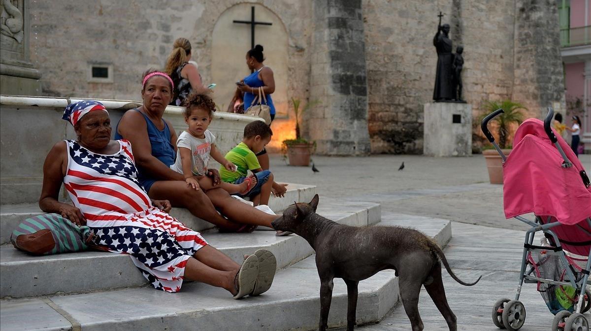 Una mujer con un vestido con la bandera de Estados Unidos descansa en una plaza de la Habana.
