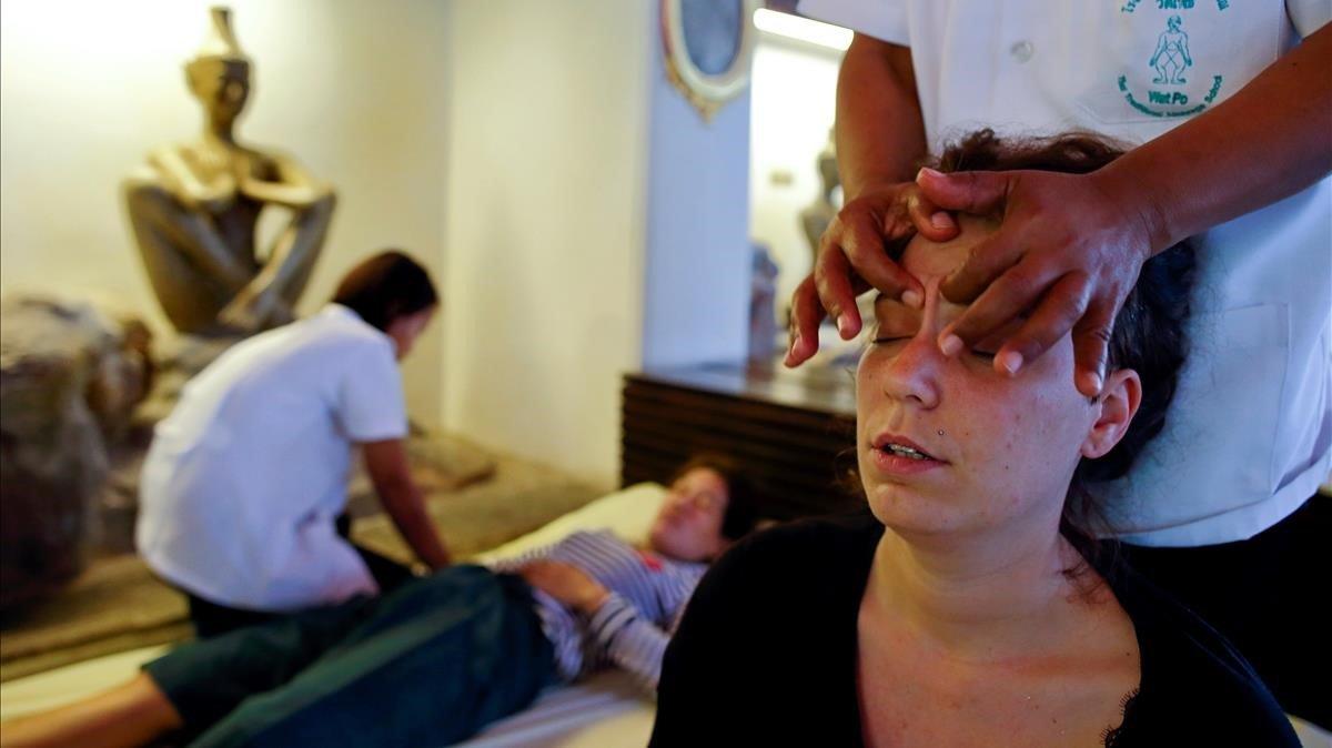 Un turista recibe un masaje tradicional tailandés en un templo de Bangkok