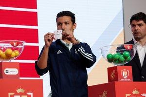 El futbolista internacional del Sevilla Jesús Navas muestra el nombre de un equipo en el último sorteo de la Copa del Rey.