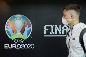 Un viajero pasa por delante de un anuncio de la Eurocopa en el aeropuerto de Bucarest, en Rumanía.