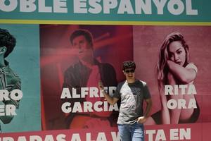 El exconcursante de O.T., Alfred García, junto al cartel del evento.