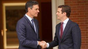 El presidente del Gobierno en funciones, Pedro Sánchez, saluda al líder del PP, Pablo Casado, este lunes en la Moncloa.