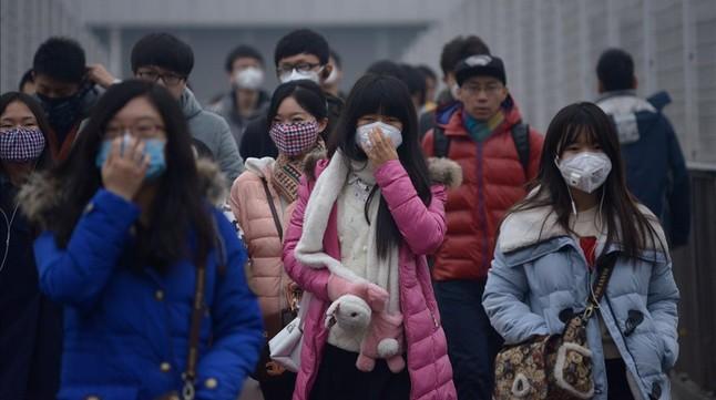 Un grupo de peatones cruza las calles de Pekín protegidos con máscaras