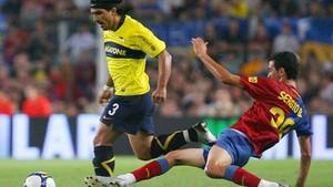 Sergio Busquets hace una entrada ante un futbolista de Boca Juniors.