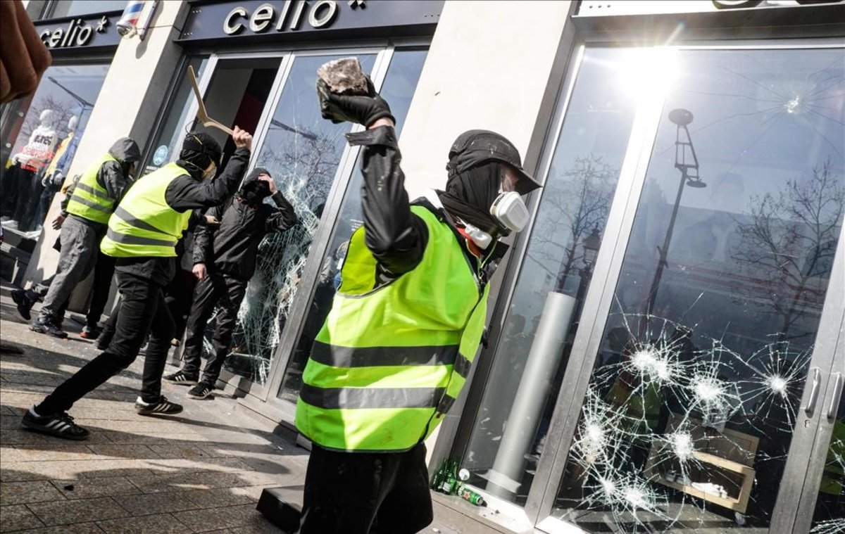 Un chaleco amarillo rompe el cristal de una tienda en los Campos Elíseos de París.