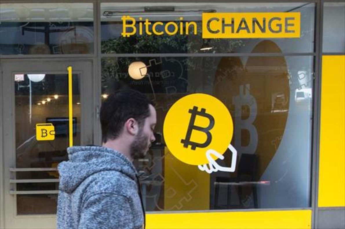 Un ciudadano israelí pasa delante de una oficina de cambio de bitcoines, en Tel-Aviv.